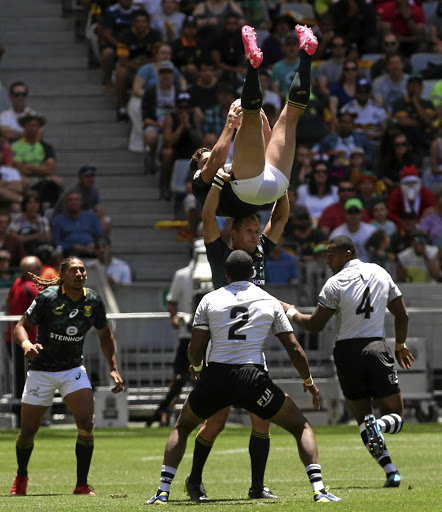 SA turned upside down: Kwagga Smith is supported by Blitzbok captain Philip Snyman while team-mate Justin Geduld, left, looks on in the quarterfinal against Fiji. Picture: ESA ALEXANDER