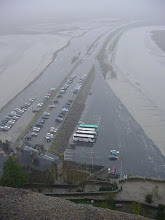 Photo: Monday morning dawns cold and rainy, and after a two-hour drive, we arrive at Mont-St-Michel. This view from near the entrance to the Abbey looks down on the parking lot, where our red Citroen van can be clearly seen at the entrance. Only in November could one get such a choice parking spot! We are here at low tide, and must leave by late afternoon, as this lot will be under water by early evening.