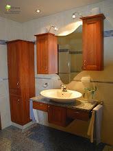 Photo: In Birnbaum massiv im Landhausstil. Der Spiegel in Form einer welle stellt eine schöne Verbindung zwischen den beiden Hängeschränken her.