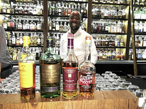 Whiskey fundi Valentine Maseko serves whiskey patrons with a smile.