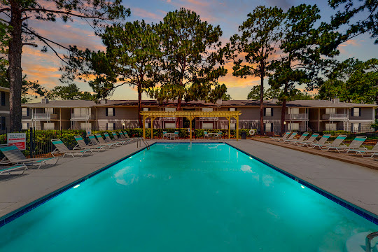 Apartment swimming pool with patio furniture at dusk