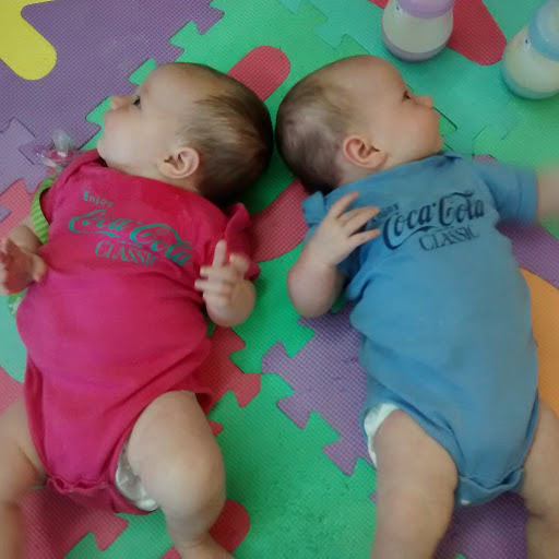 Baby twin girls in onesies with Hebrew writing
