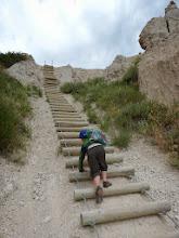 Photo: Quinn climbing a ladder while hiking in Badlands
