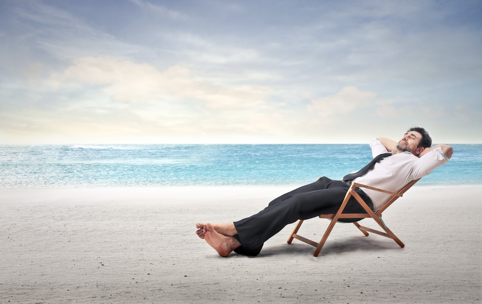 Man in business clothes in a lounge chair vacationing on the beach