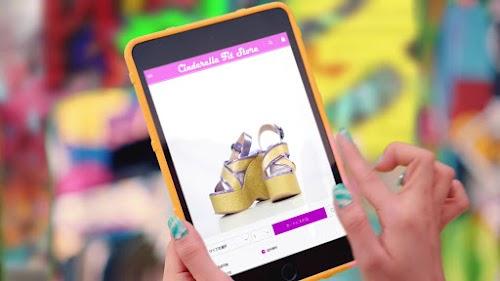 """YURINO escolhendo um calçado no tablet. Detalhe: o nome da loja é """"Cinderella Fit Store""""."""