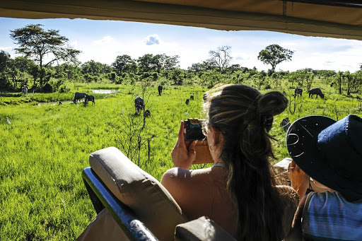Visitors return: Tourists photograph wild animals during a drive in a private game reserve outside Harare, Zimbabwe, in December 2017. Tourism is seen as a creator of jobs in a country with a 90% unemployment rate. Picture: BLOOMBERG