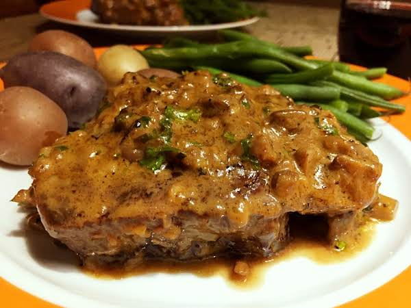 A Steak Topped With A Brown Sauce On A Plate Along With Green Beans And Small Potatoes.