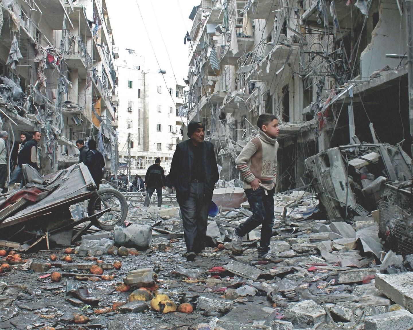 An older man and young boy walking on a ravaged city street with destroyed buildings all around