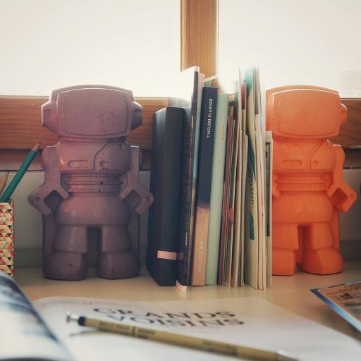 idée déco serre-livre avec deux figurines déco en béton en forme de robot pour une déco geek