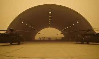Apache helicopters and hangar in a dust storm in Iraq.