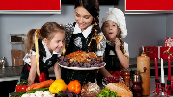 a woman and two girls preparing food for Thanksgiving
