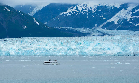 A small tour boat passes along the edge of Hubbard Glacier in Alaska.