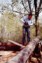 Photo: Drilling for rods to tie logs together.