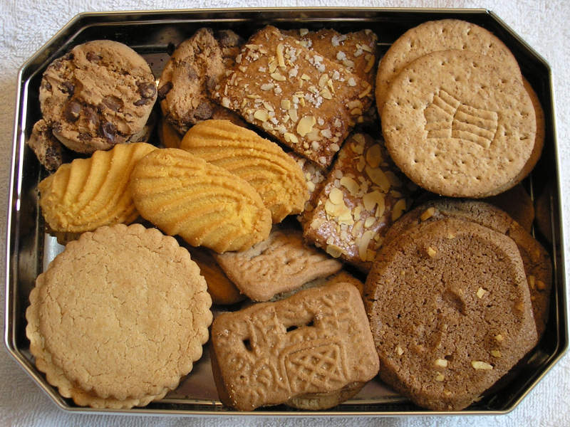 A silver tray holding a variety of different types of cookies.