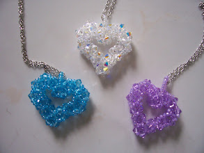 "Photo: Swarovski Crystal Open Heart. Size: 1 1/4"" wide x 1 3/8"" long x 1/4"" thick. Color left to right: Aquamarine, Clear AB and Violet. $45.00 each."