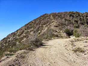 Photo: From the same location, view southwest as the road reaches the ascending/descending ridge on the northeast hip of Sunset Peak. That faint path provides an alternate route straight up the ridge 420 vertical feet to the summit.