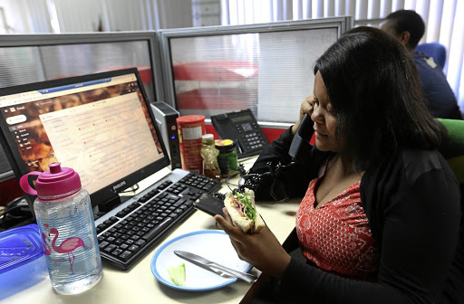 Lwandile Bhengu eats lunch on the job. Many people do not have time for lunch breaks.