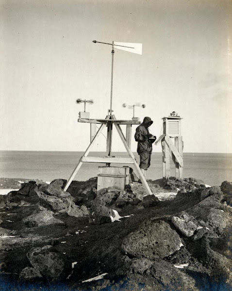 Photo: Dr Simpson taking meteorological observations at the station on Vane Hill, Cape Evans. Image courtesy of the Royal Geographical Society.