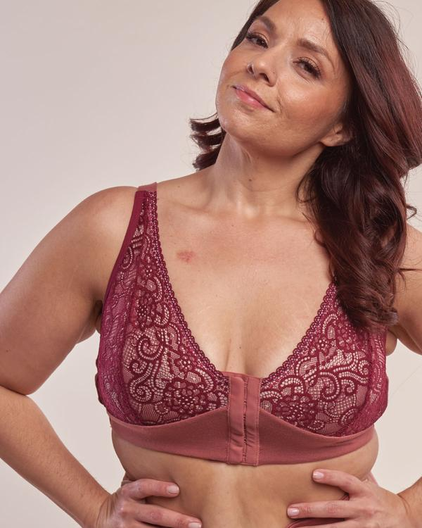 A survivor of breast cancer poses wearing a red lace bra with hooks in the front.