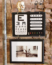 """Photo: An antique eye chart (""""It still lights up!"""") hangs above a childhood photo of Crow's father in the hall."""