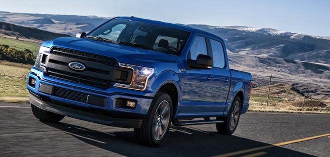A blue F-150 pickup truck drives down a Saskatchewan Highway