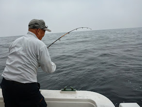 """Photo: おおーっ! まだ他の皆さん、釣りの準備をしてるのにもうフィーッシュの""""イノウエさん""""! ・・・船頭さんのお株をうばう「ジギング」でのヒット!"""
