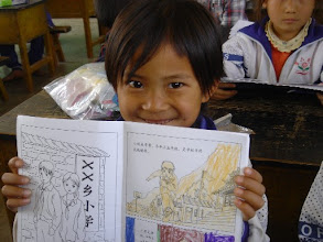 Photo: A Yunnan Province child showing off her coloring in the health book