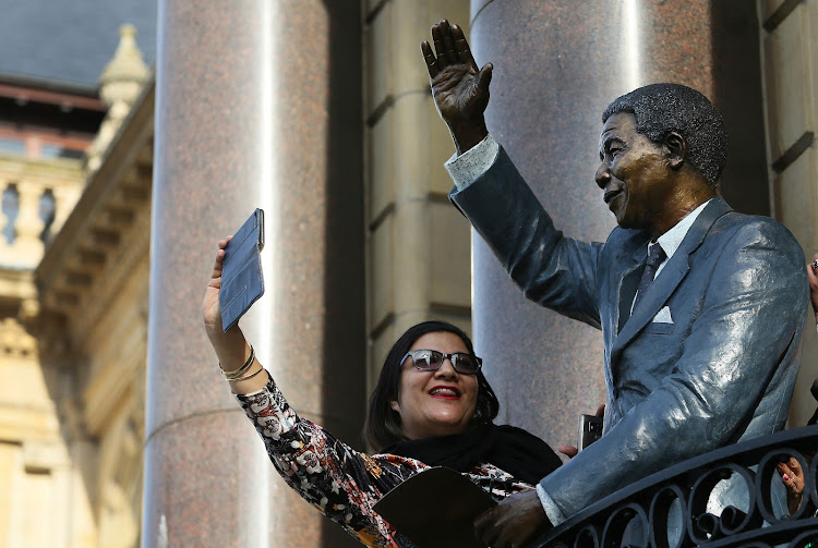 A Capetonian grabs a selfie with the statue of Nelson Mandela unveiled on Tuesday on the balcony of Cape Town City Hall, where Mandela made his first speech after his release in February 1990.