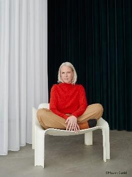 赤いカーテンの前の椅子に座る女性  低い精度で自動的に生成された説明