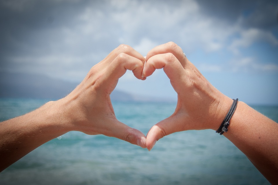 two hands making a heart shape with sea in background