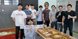 """The employees and founders of the Motion2ai startup are holding up a """"Motion2ai"""" sign at a party."""