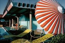 half verborgen tegen elkaar aangedrukt paar aan de rand van een zwembad met supergrote liggende parasol
