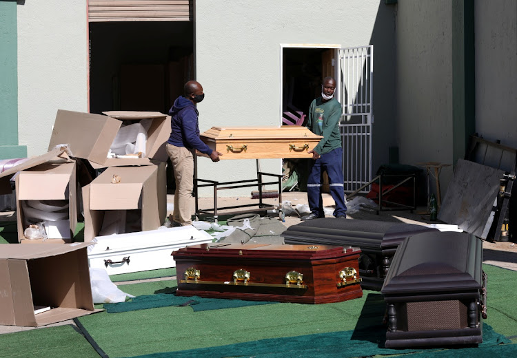 Workers carry a coffin after assembling it at Avbob Funerals in Midrand, amid a rise in Covid-19 infections nationwide. Picture: REUTERS/Siphiwe Sibeko