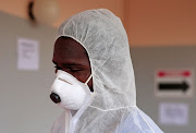 A Zimbabwean health worker wears a protective suit during a training exercise aimed at preparing workers to deal with potential coronavirus cases. SA has confirmed seven cases of the virus.