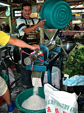 Photo: milking grated coconut with a mechanical press, Khorat market
