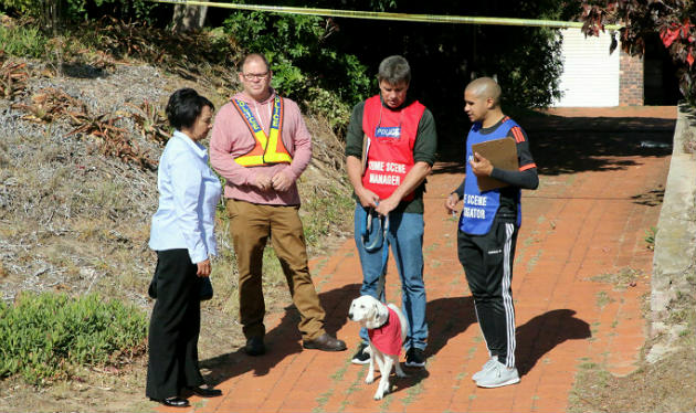 Brigadier Leonie Bentley, left, and other police at the scene with Ann Ferreira's dog, Tory