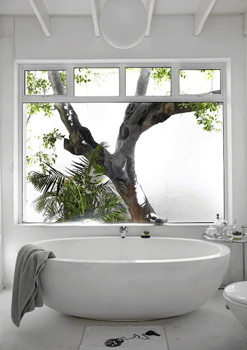 The all-white bathroom was fully renovated to incorporate a contemporary tub and large window.