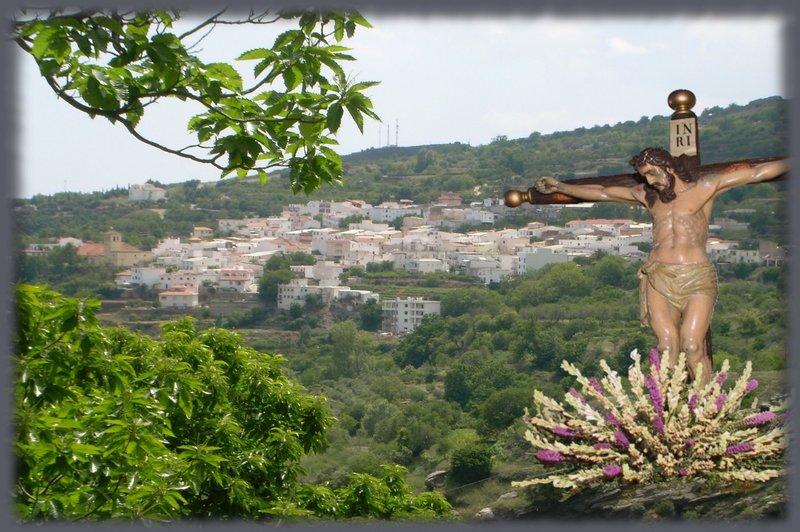 Imagen del Santo Cristo de las Penas, Patrón de Paterna del Río, con el pueblo al fondo