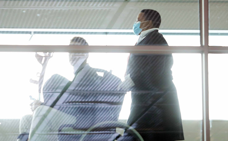 People at Cape Town International Airport wear face masks on March 6 2020.