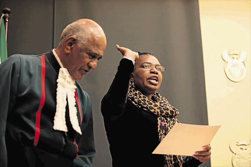 Constitutional Court Justice Zak Yacoob swears in Dina Pule as the new Minister of Communications at Tuynhuys yesterday Picture: SHELLEY CHRISTIANS