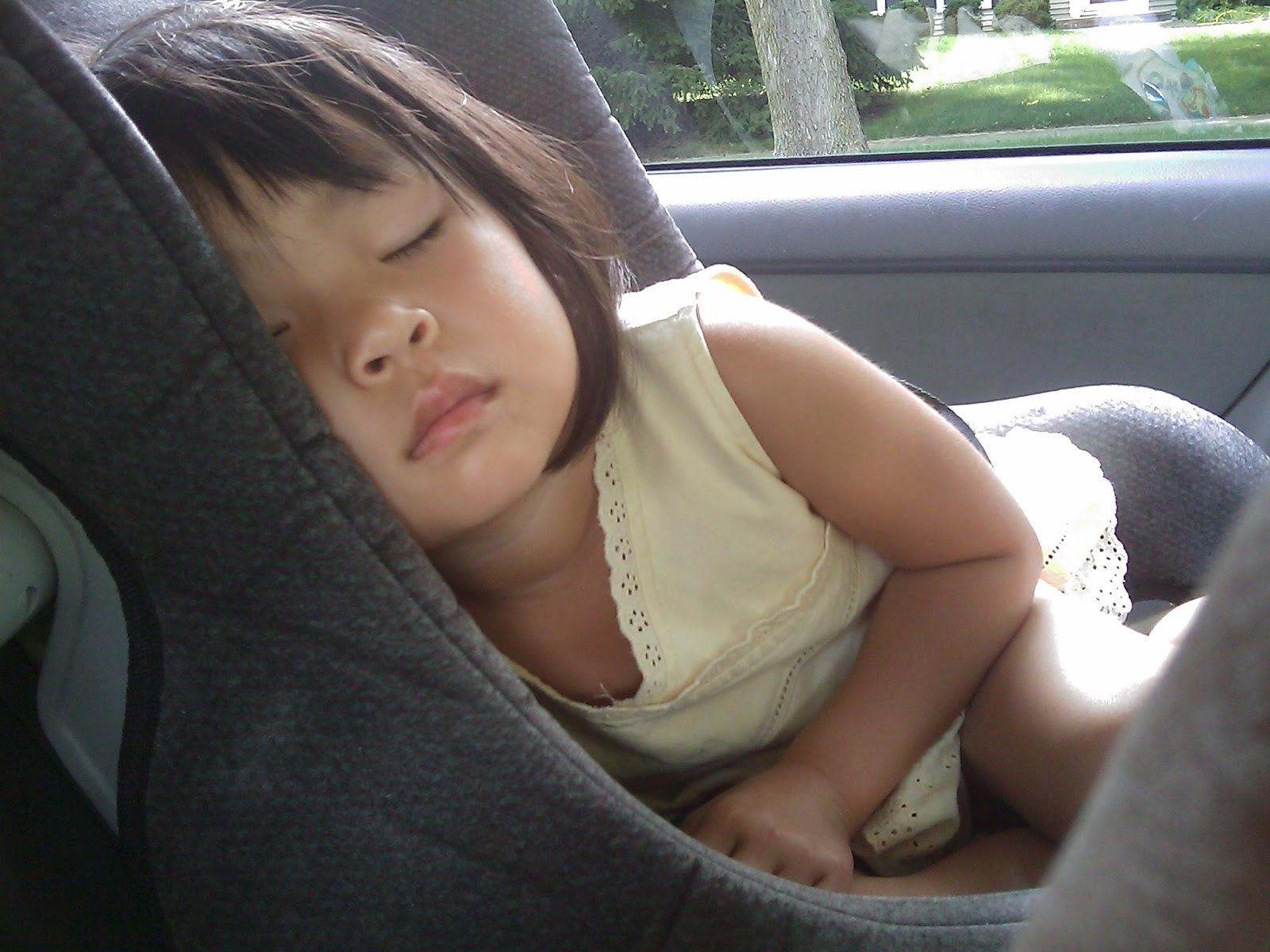 Criança dormindo de lado em uma cadeirinha de bebê no Uber e 99.