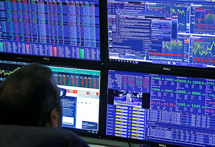 Traders work at their desks while screens show market data at CMC Markets in London, the UK. Picture: REUTERS/HENRY NICHOLLS