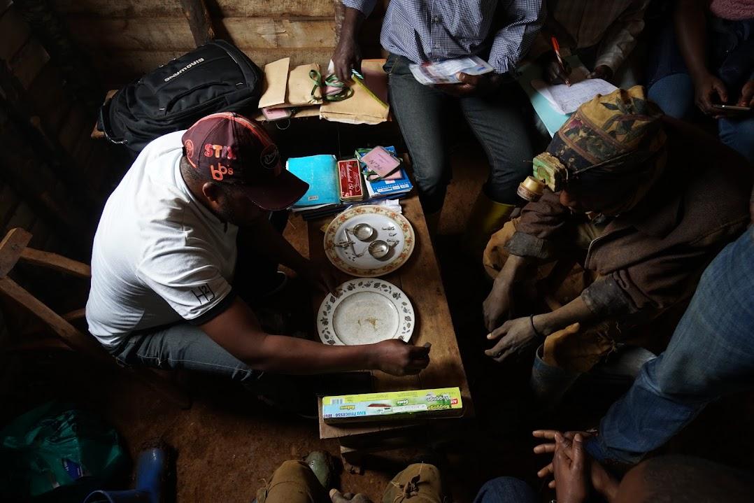 テーブルを囲んで金取引を記録し、トレーサビリティを確保する人々。