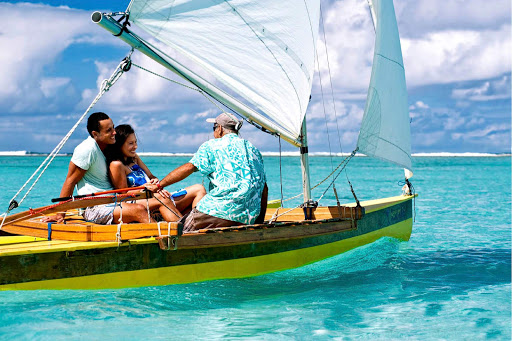Hop into a sailboat and glide over turquoise waters along a secluded beach in the Cook Islands.
