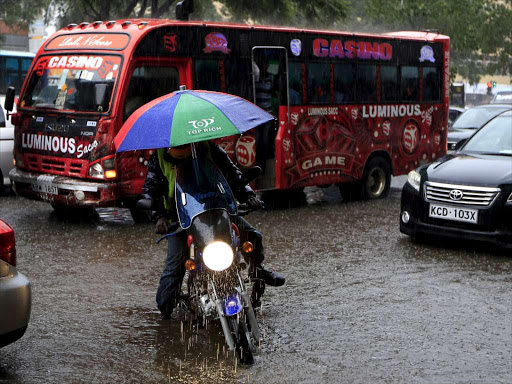 A motorcyclist wades through water during heavy rains in Nairobi./FILE