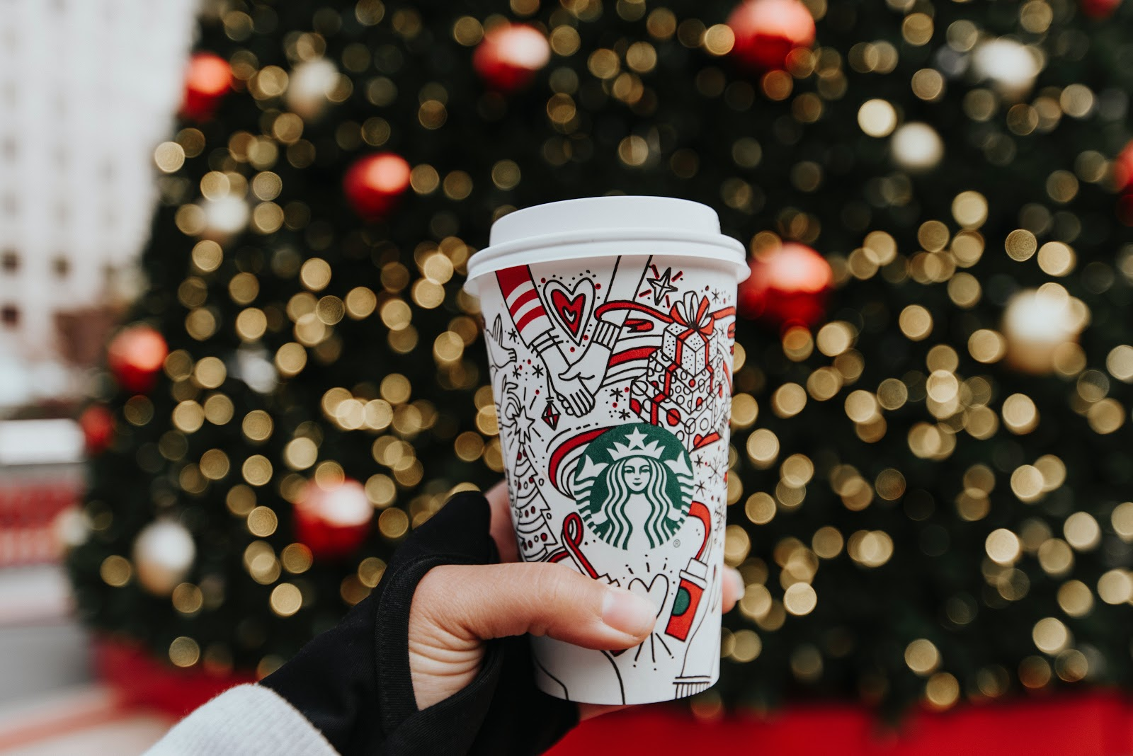 A hand holding a decorated coffee cup in front of a Christmas tree.