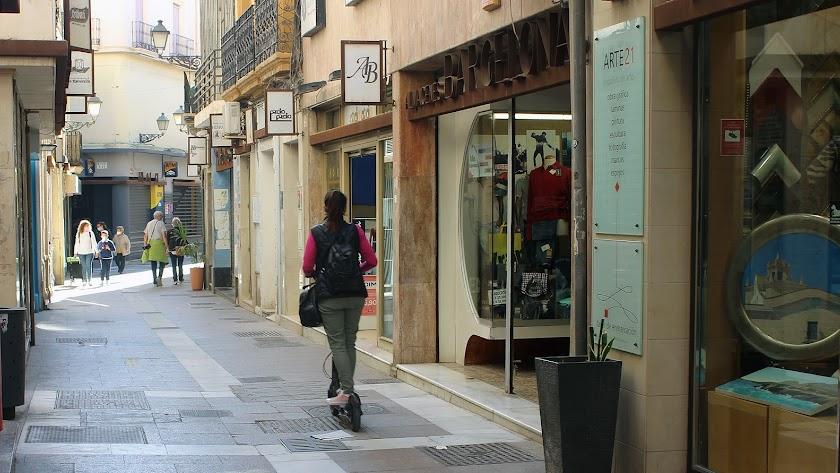 Una joven en patinete por el centro de la ciudad.
