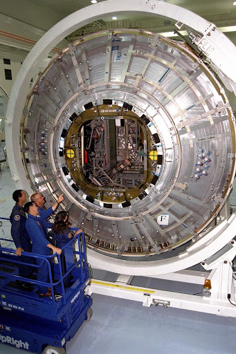 Members of the crew examine the Node 1 of the Internation Space Station in the high bay of the Space Station Processing Facility.