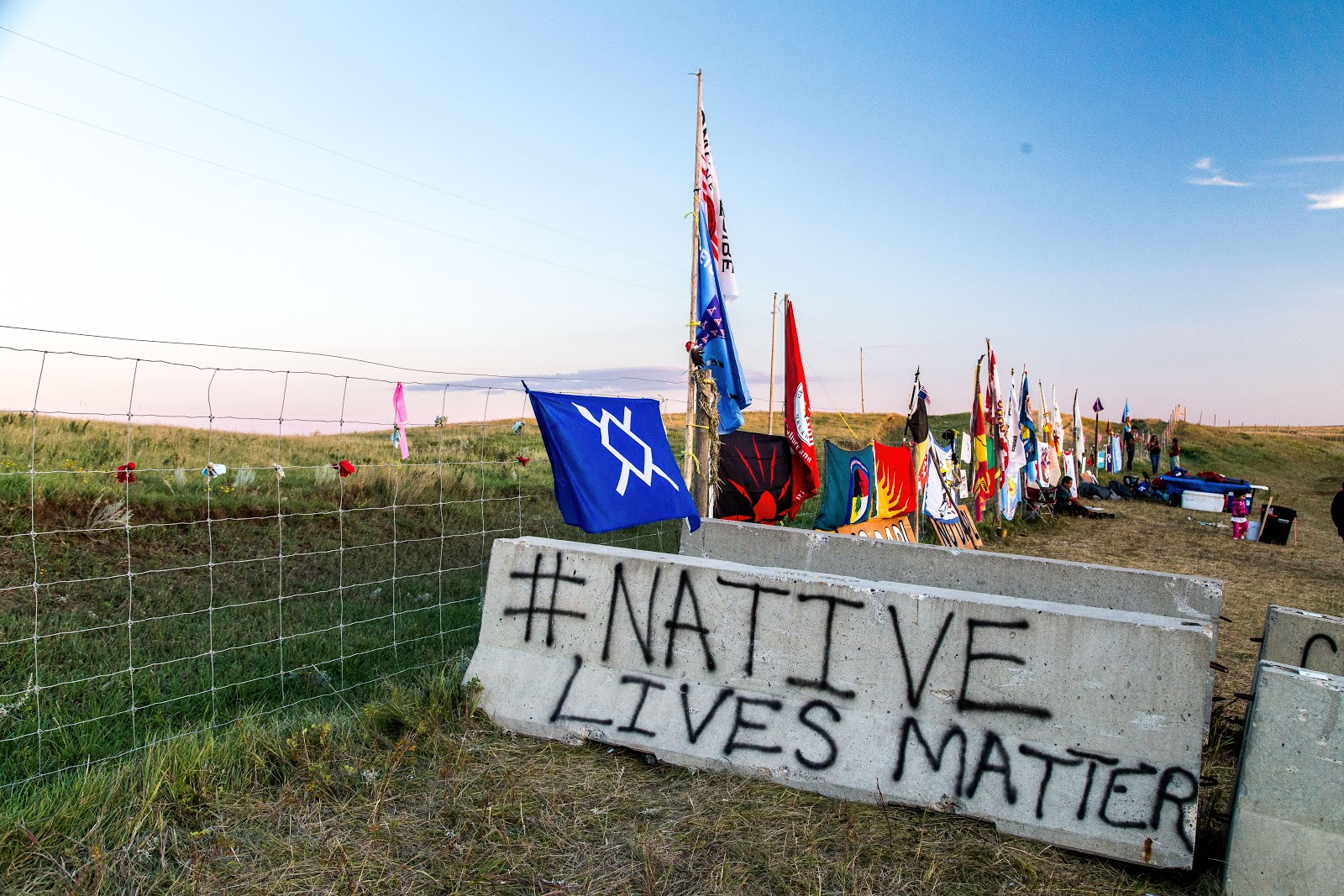 Flags from many nations line the fence outside the Dakota Access pipeline construction site. (Photo: Alex Hamer)