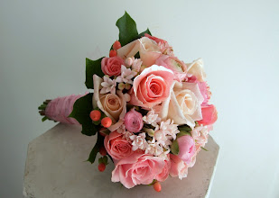 Photo: [B11] Hand tied bouquet with partial stem wrap of peach, pink, and white roses with white bouvardia, pink hypericum, and ranunculus, surrounded by salal leaves
